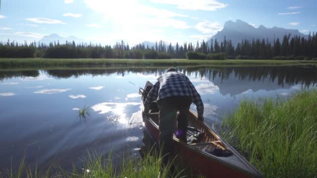 man paddles wooden canoe into mountain lake - pushing stock videos & royalty-free footage