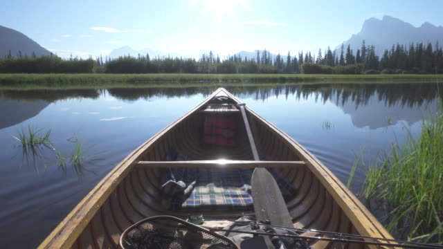 Man paddles wooden canoe into mountain lake
