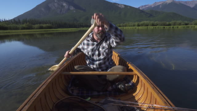 man paddles wooden canoe into mountain lake - rowing boat stock videos & royalty-free footage