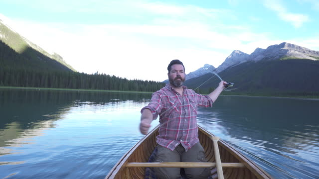 vidéos et rushes de man paddles wooden canoe into mountain lake, with fishing gear - bateau à rames