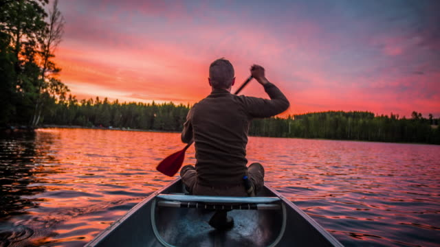 man paddling a canoe at sunset - pov - avventura video stock e b–roll