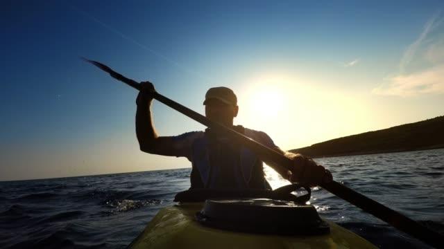 vidéos et rushes de ld man pagayer un kayak de mer le long de la côte - kayak sport
