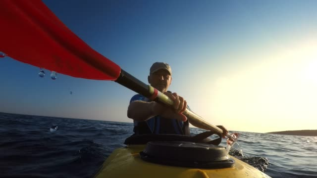 ld man paddling a sea kayak at sea in late afternoon sun - hobbies stock videos & royalty-free footage