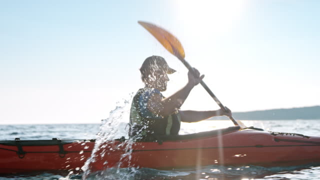 slo mo man paddling across the sea in his sea kayak on a sunny day - kayak video stock e b–roll