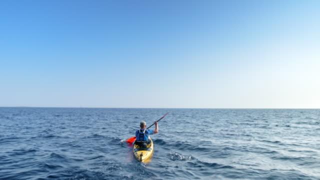 man paddling his kayak at sea in sunshine - hobbies stock videos & royalty-free footage