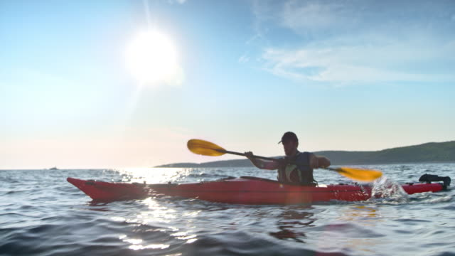 slo mo man paddling his touring kayak across the sunny sea - giacca di salvataggio video stock e b–roll