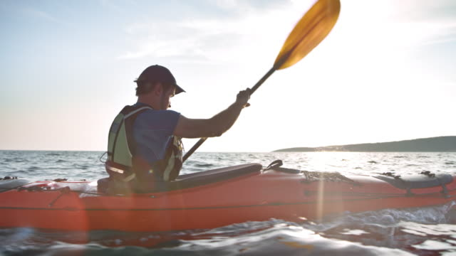 vídeos de stock e filmes b-roll de slo mo ts man paddling in his touring kayak at sea in sunshine - kayaking