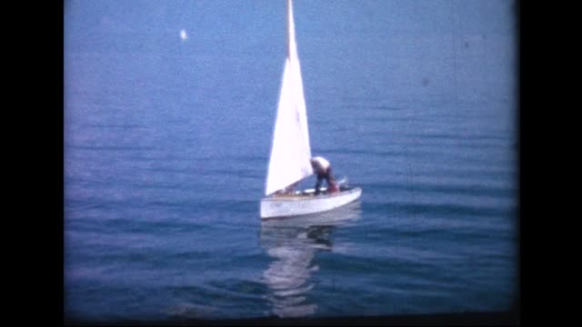 1964 man paddling small sailboat to dock in Lac de Joux