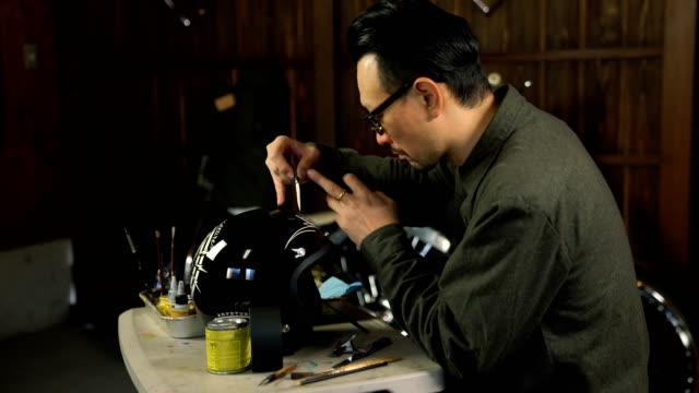 mann malerei benutzerdefinierte grafik auf ein motorrad-helm - sturzhelm stock-videos und b-roll-filmmaterial