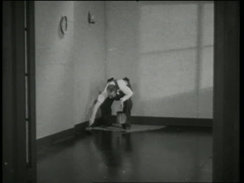 b/w 1935 man painting floor paints himself into corner / why pay rent? - decorating stock videos & royalty-free footage