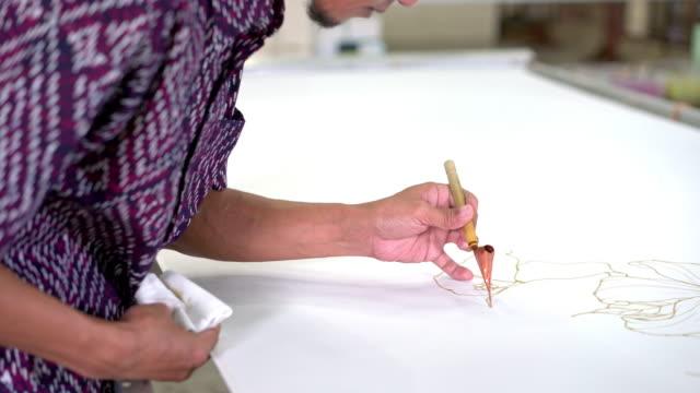 man painting in a batik workshop - kuala lumpur stock videos & royalty-free footage