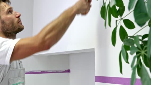 stockvideo's en b-roll-footage met man schilderij van de muur wit met een schilderij roller - schilderen