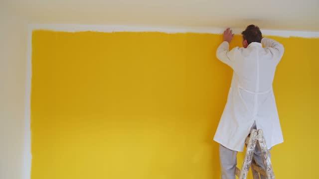 stockvideo's en b-roll-footage met mens die hoogste randen van de muur in gele kleur schildert. hij staat op de houten ladder. - doe het zelven