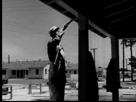 1935 ms man painting trim of house roof on site of tract housing development/ usa  - bib overalls stock videos and b-roll footage
