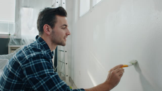 man painting wall at home - one young man only stock videos & royalty-free footage