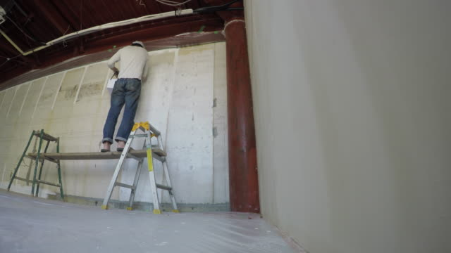 Man painting wall with paint brush in own shop