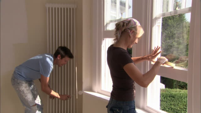 Man painting wall with paint roller as woman applies masking tape to window frame in preparation for painting