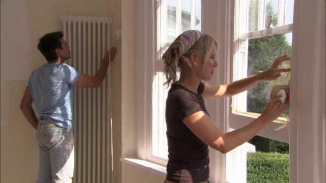 man painting wall with paint roller as woman applies masking tape to window frame in preparation for painting - window frame stock videos and b-roll footage