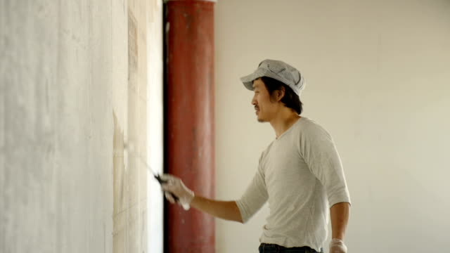 Man painting wall with paint roller in own shop