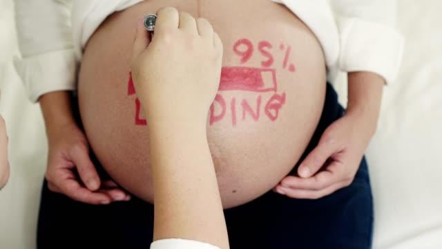 mann malt auf bauch der schwangeren frau - schwanger stock-videos und b-roll-filmmaterial