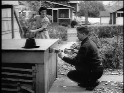 B/W 1943/44 man paints porch as woman sweeps / Springfield, NJ / newsreel