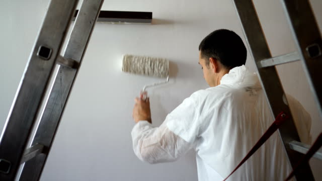 man paints the walls of  home with paint roller - decorating stock videos & royalty-free footage