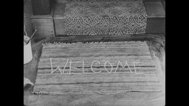 1920 man (buster keaton) paints welcome upside down on a door mat at the bottom of the staircase and turns the rug around to make the word right side up - welcome mat stock videos and b-roll footage