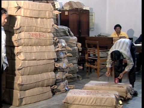 man paints words on burlap sacks. - 荒い麻布点の映像素材/bロール