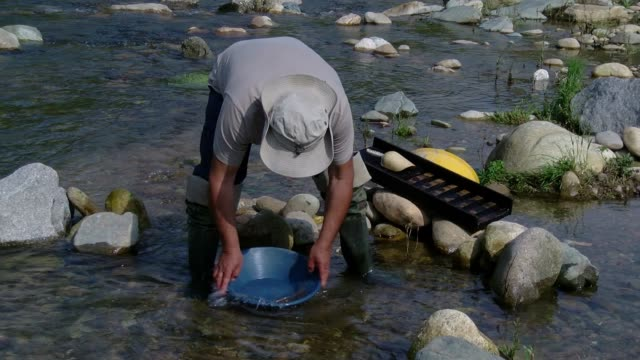 Man Pans Gold From a River In Zubiena, Italy