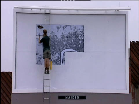 man papers london map on billboard - poster stock videos and b-roll footage