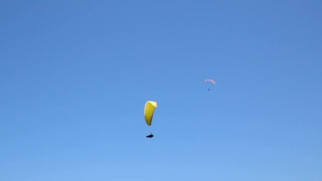 paragliding in blauen himmel - fallschirm stock-videos und b-roll-filmmaterial