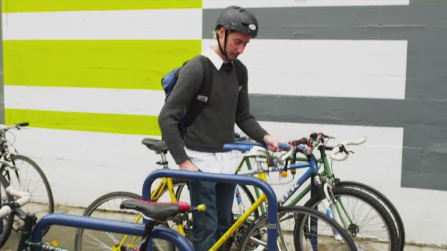 MS TS ZI ZO TU TD Man parking bicycle and locking it / Portland, Oregon, USA