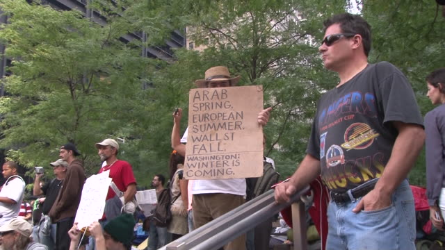 man partially obscures his face with a protest sign during the occupy wall street movement in zuccotti park. - occupy protests stock videos & royalty-free footage