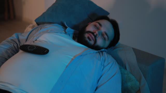 vídeos de stock, filmes e b-roll de homem desmaiou no sofá - devagar