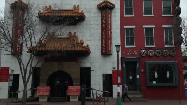 man passes through a quiet chinatown april 1, 2020 in washington, dc. the district of columbia has joined other states and territories, including... - maryland stato video stock e b–roll