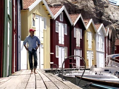 vídeos y material grabado en eventos de stock de a man passing by fishing-huts smogen bohuslan sweden. - un solo hombre de mediana edad