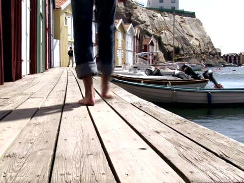 A man passing by fishing-huts Smogen Bohuslan Sweden.
