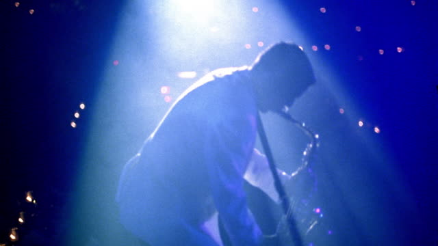 blue ms silhouette profile man passionately playing saxophone on stage with spotlight / turns - saxophone stock videos and b-roll footage