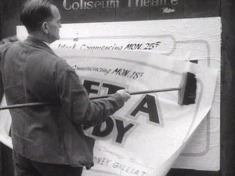 a man pastes a poster onto a billboard advertising a new theatrical production at the coliseum theatre in oldham - poster stock videos & royalty-free footage