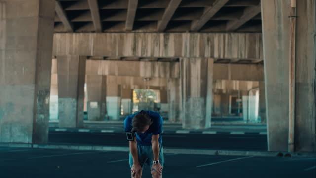 Man pauses jogging in urban setting