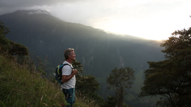 Man pauses on mountain slope, looking to sunrise