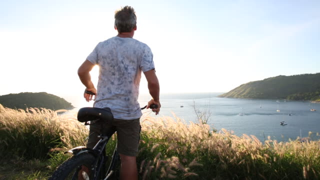 Man pauses with bike at viewpoint, looks over sea