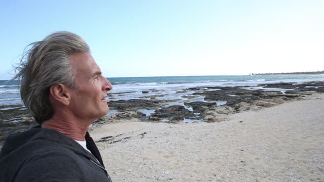 POV of man pausing with bicycle on beach, looking off