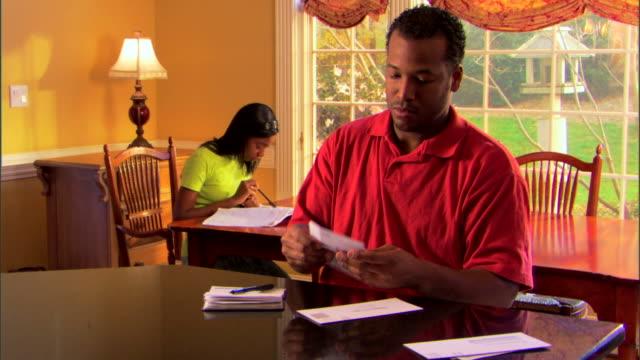 man paying bills and daughter doing homework - envelope stock videos & royalty-free footage