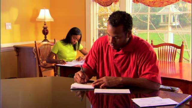 man paying bills and daughter doing homework - andere clips dieser aufnahmen anzeigen 1282 stock-videos und b-roll-filmmaterial