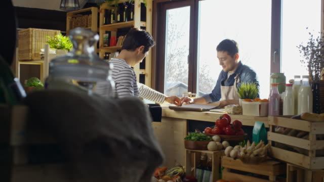 vídeos y material grabado en eventos de stock de man paying for purchase at grocery store - tienda de fruta y verdura