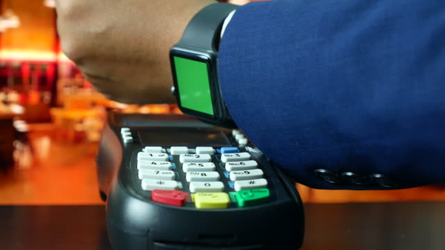 Man Paying With NFC Technology on Smart Watch Green screen in restaurant, Contactless payment