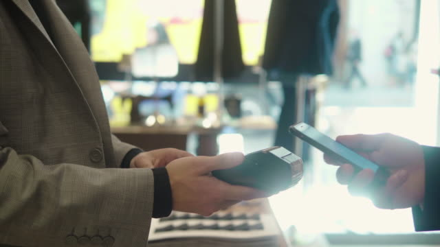 vídeos de stock e filmes b-roll de man paying with smartphone at the menswear store - boutique