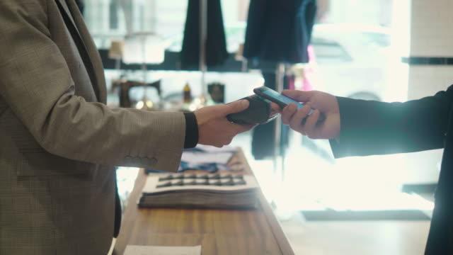 vídeos de stock e filmes b-roll de man paying with smartphone at the menswear store - loja de roupa