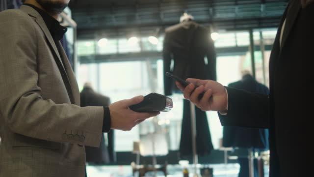 vidéos et rushes de homme payant avec le smartphone au magasin de vêtements pour hommes - manteau et veste
